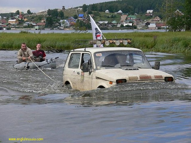 "Russian SUV ""Niva"" towes a boat"