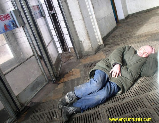 man laying against the entrance to the moscow city subway
